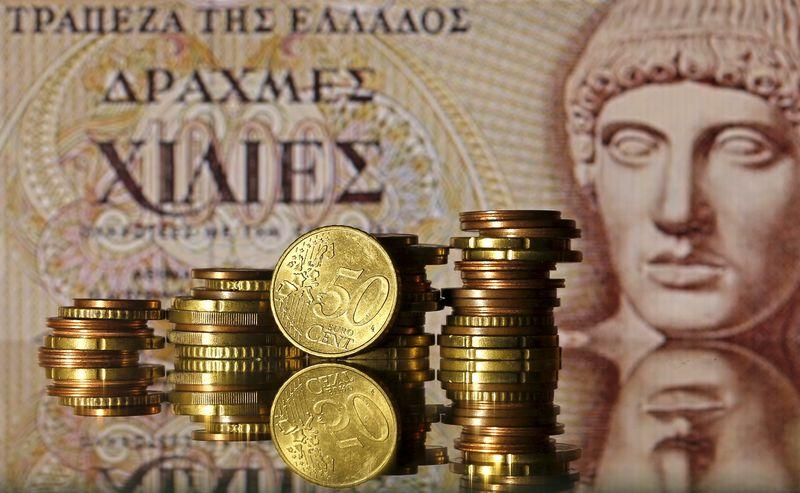 Euro coins are seen in front of a displayed of Head of Apollo on 1.000 Drachma old Greece banknote in this photo illustration taken in Zenica