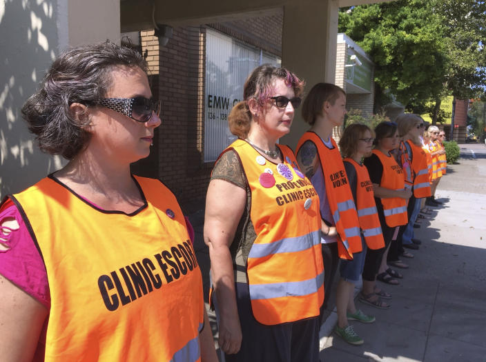 FILE - In this July 17, 2017 file photo, escort volunteers line up outside the EMW Women's Surgical Center in Louisville, Ky. A federal judge in Kentucky has cautioned lawyers to watch their language in their bitter legal feud over abortion, this time over a lawsuit challenging two new state laws aimed at putting more restrictions on the procedure. (AP Photo/Dylan Lovan, File)