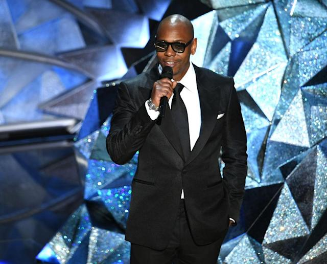 <p>Dave Chappelle wears oversize square glasses with his black suit while presenting at the 2018 Oscars. (Photo: Getty Images) </p>