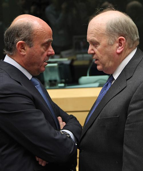 Spanish Economy Minister Luis de Guindos Jurado, left, talks with Irish Finance Minister Michael Noonan, during the EU finance ministers meeting, in Brussels, Wednesday, June 26, 2013. European Union finance ministers are making a fresh attempt to set up rules on how to distribute the cost of failing banks without letting taxpayers foot the bill. The EU's 27 finance ministers are set to gather for an emergency meeting in Brussels after they failed to reach an agreement on the legislation in 19 hours of negotiations last week. (AP Photo/Yves Logghe)