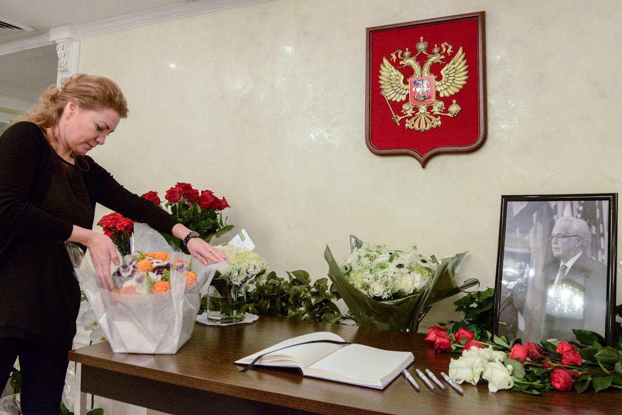A woman sets out flowers for a memorial to Russia's recently deceased ambassador to the United Nations, Vitaly Churkin, at the Russian mission to the United Nations in New York City, U.S. February 21, 2017. REUTERS/Stephanie Keith
