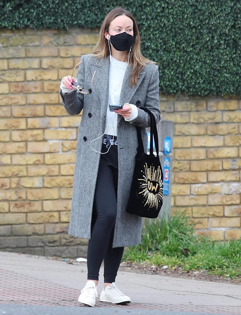 <p>Olivia Wilde is plugged into her phone as she steps out Wednesday morning to grab coffee in London.</p>