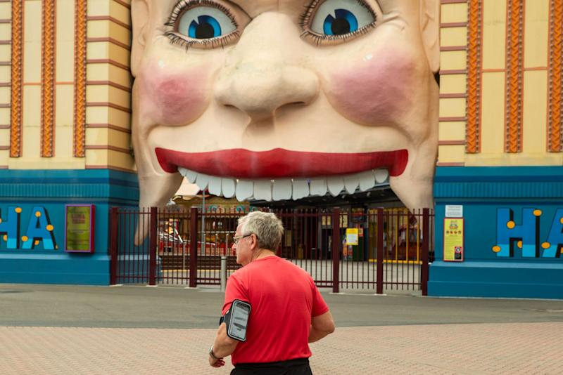A man is seen jogging past a closed Luna Park in Sydney.