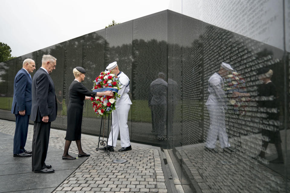 Cindy McCain, wife of, Sen. John McCain, R-Ariz., accompanied by President Donald Trump's Chief of Staff John Kelly, left, and Defense Secretary Jim Mattis, second from left, lays a wreath at the Vietnam Veterans Memorial in Washington, Saturday, Sept. 1, 2018, during a funeral procession to carry the casket of her husband from the U.S. Capitol to National Cathedral for a Memorial Service. McCain served as a Navy pilot during the Vietnam War and was a prisoner of war for more than five years. (AP Photo/Andrew Harnik, Pool)