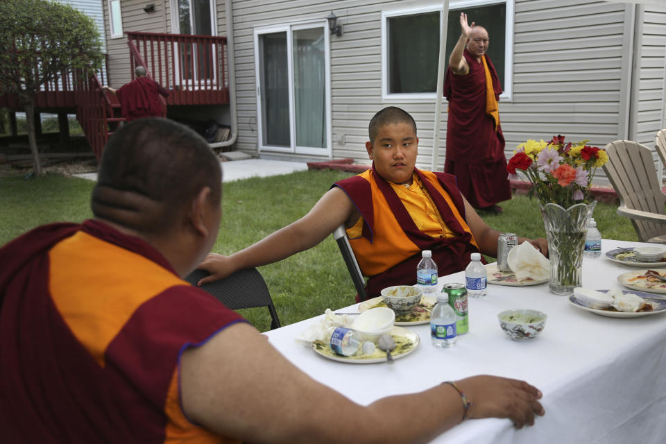 Tibetan Buddhism meditation and mentor Khenpo Kunga, left, talks with 14-year-old Buddhist lama Jalue Dorje after a dinner on Monday, July 19, 2021 in Columbia Heights, Minn., concluding a ceremony paying homage to Guru Rinpoche, the Indian Buddhist master who brought Tantric Buddhism to Tibet. (AP Photo/Jessie Wardarski)