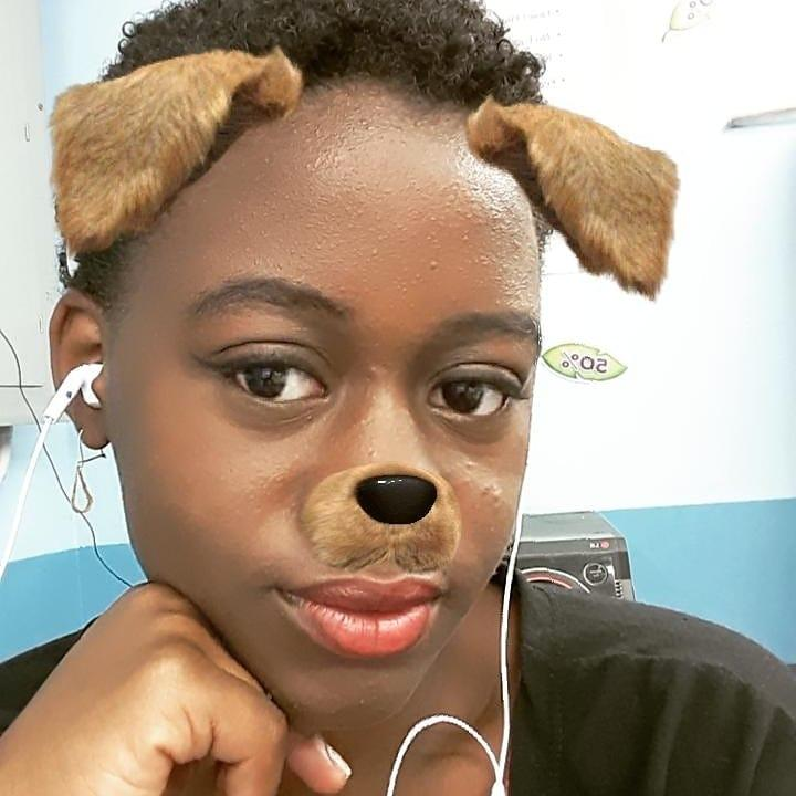 """woman using """"dog face"""" snapchat filter. Resting head on hand with short hair"""