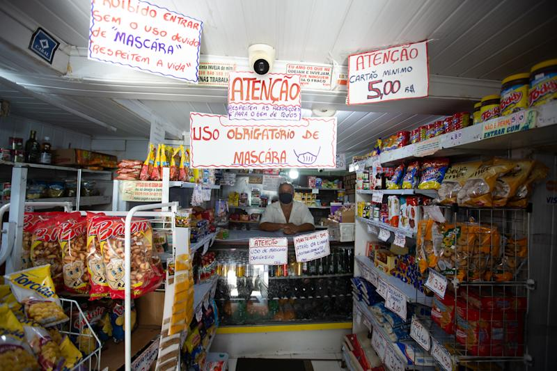 "SAO PAULO, BRAZIL - MAY 16: The owner of a grocery store wearing a face mask looks on behind the counter under a sign that reads ""Mandatory use of mask"" amidst the coronavirus (COVID-19) pandemic on May 16, 2020 in Brasilandia, Sao Paulo, Brazil. Brasilandia is the neighborhood of Sao Paulo with the highest number of confirmed deaths by coronavirus (COVID-19), with at least 185. Brasilandia is a very popular area and has a large amount of local commerce, churches and street markets, which remain open during the pandemic, even with a government decree that states that only essential services should operate. According to the Brazilian Health Ministry, Brazil has over 399,000 positive cases of coronavirus (COVID-19) and more than 25,000 deaths. (Photo by Alexandre Schneider/Getty Images)"