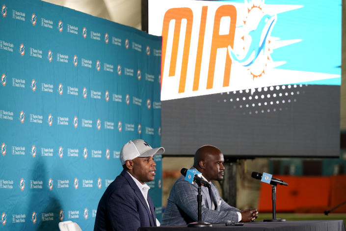 Miami Dolphins general manager Chris Grier, left, and coach Brian Flores speak during a news conference about players chosen by the Dolphins in the first round of the NFL football draft, early Friday, April 30, 2021, in Davie, Fla. (AP Photo/Lynne Sladky)