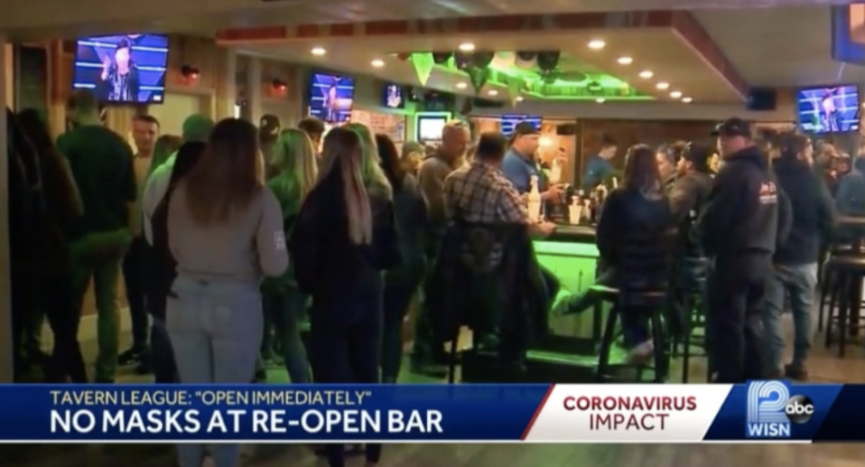 "A news reel showing a packed Wisconsin bar. ""No mask at re-open"" it says."