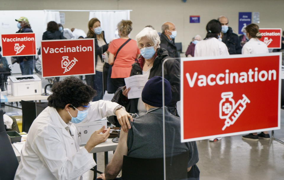A man receives his COVID-19 vaccine at a clinic at Olympic Stadium marking the beginning of mass vaccination in the Province of Quebec based on age in Montreal, on Monday, March 1, 2021. (Paul Chiasson/The Canadian Press via AP)