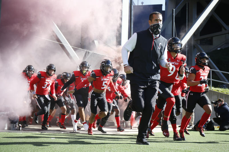 Cincinnati head coach Luke Fickell, front right, leads the team onto the field against Memphis before the start of an NCAA college football game Saturday, Oct. 31, 2020, in Cincinnati. (Photo by Gary Landers)