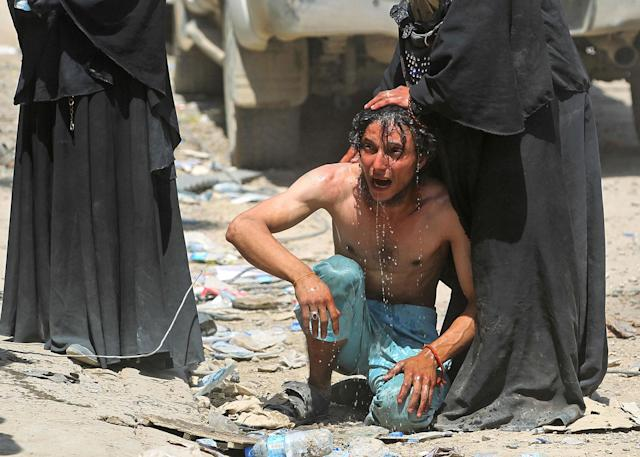<p>An Iraqi woman pours water to calm down a civilian, who witnessed a suicide attack as people were escaping the Old City of Mosul, as he cries on June 23, 2017.<br> (Photo: Ahmad al-Rubaye/AFP/Getty Images) </p>