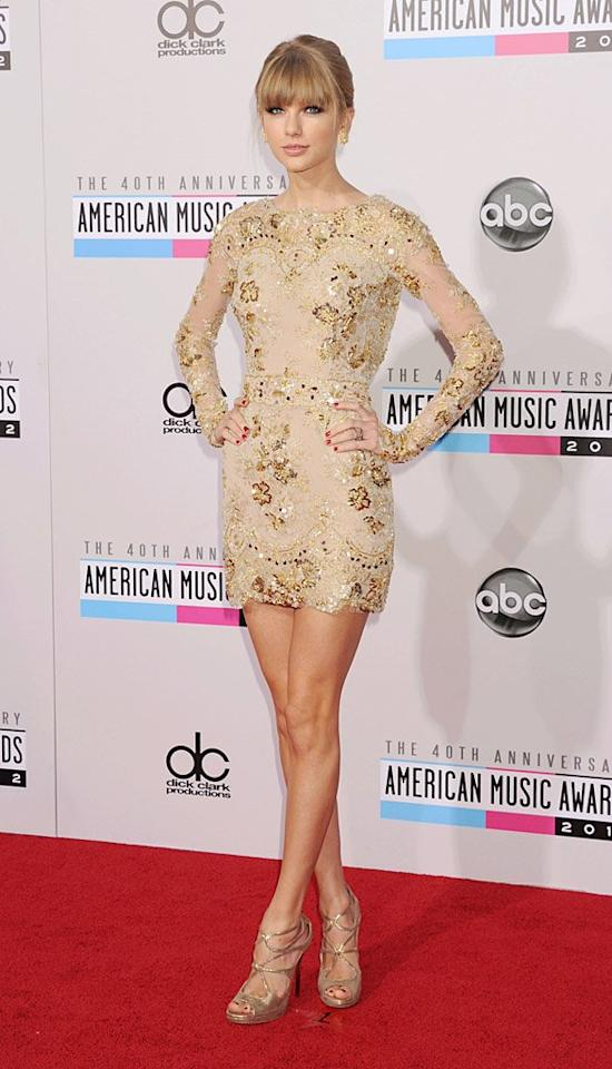 """Taylor Swift – who recently gushed about her love of dresses – surprised us when she stepped onto the red carpet at the American Music Awards in this sexy Zuhair Murad mini. While she has been wearing lots of metallics lately, the form-fitting design was a bold departure from what we're used to seeing the """"Red"""" songstress sport. Though she's known to be a big fan of flared frocks and long gowns that occasionally feature trains, Swift looked absolutely stunning in the lace dress, which hugged her body perfectly and allowed her to flaunt her endless legs. (11/18/2012)"""