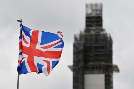 A Union Jack flag flutters as Big Ben clock tower is seen behind at the Houses of Parliament in London