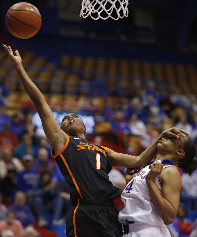 Oklahoma State guard Brittany Atkins (1) shoots while covered by Kansas guard CeCe Harper (24) during the first half of an NCAA college basketball game in Lawrence, Kan., Wednesday, Jan. 22, 2014. (AP Photo/Orlin Wagner)