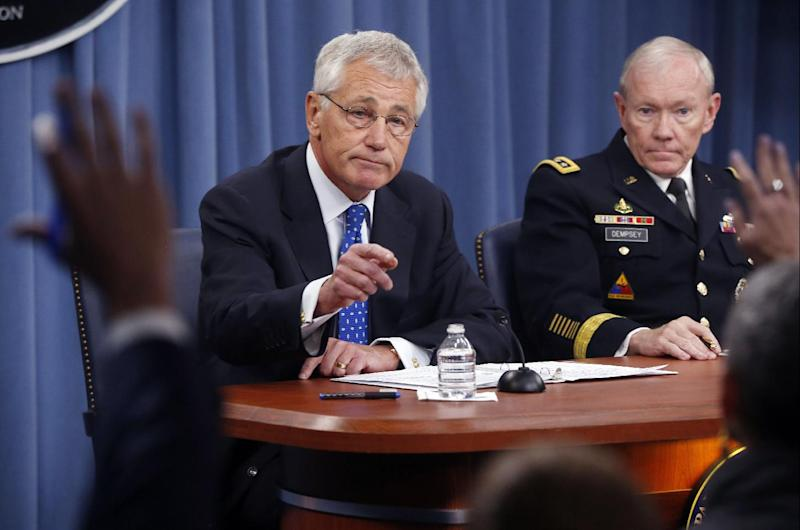 Defense Secretary Chuck Hagel and Chairman of the Joint Chiefs of Staff Gen. Martin Dempsey take questions at a news conference at The Pentagon, Wednesday, Sept. 18, 2013. Hagel is ordering the Pentagon to review the physical security of all U.S. defense facilities worldwide and the security clearances that allow access to them. Hagel ordered the reviews in response to Monday's shooting rampage at the Washington Navy Yard, where a dozen people were killed. The shooter, Aaron Alexis, also was killed. (AP Photo/Charles Dharapak)