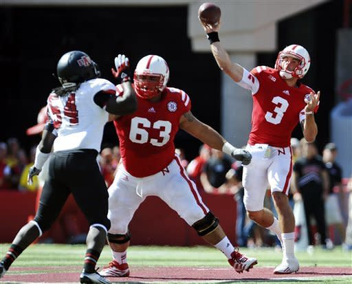 Nebraska quarterback Taylor Martinez, right, throws as Andrew Rodriguez (63) blocks Arkansas State's Shervarius Jackson (54) in the first half of their NCAA college football game in Lincoln, Neb., Saturday, Sept. 15, 2012. (AP Photo/Dave Weaver)