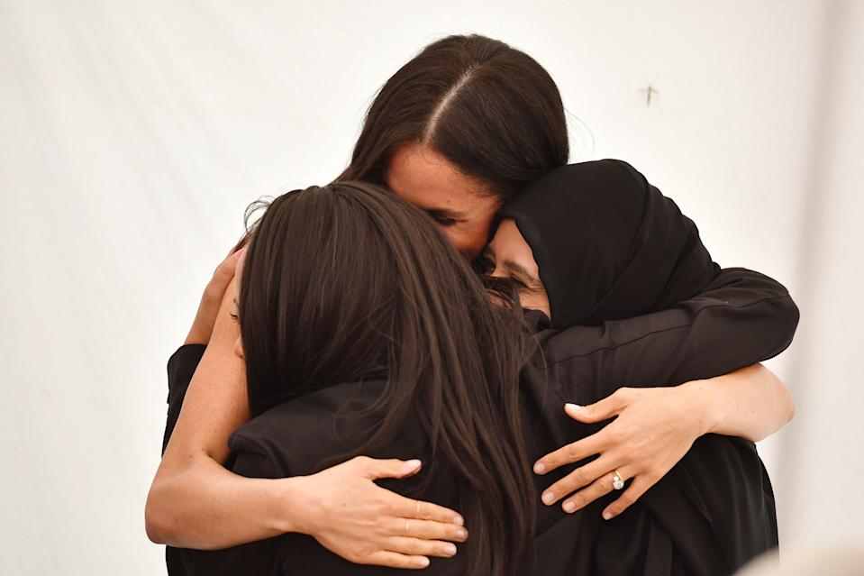 Meghan embraces women at the launch of the cookbook she has championed at Kensington Palace in London (PA)