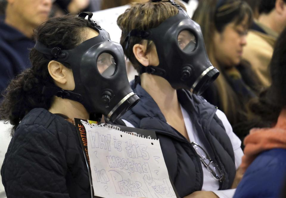 FILE - In this Jan. 16, 2016, file photo, protesters wearing gas masks, attend a hearing over a gas leak at the southern California Gas Company's Aliso Canyon Storage Facility near the Porter Ranch section of Los Angeles. Attorneys for families sickened and forced from their Los Angeles homes after the nation's largest-known natural gas leak, have reached a $1.8 billion settlement with a utility. The settlement announced Monday, Sept. 27, 2021, with Southern California Gas Co. and its parent company will compensate 35,000 plaintiffs from the 2015 blowout that took nearly four months to contain. (AP Photo/Richard Vogel, File)