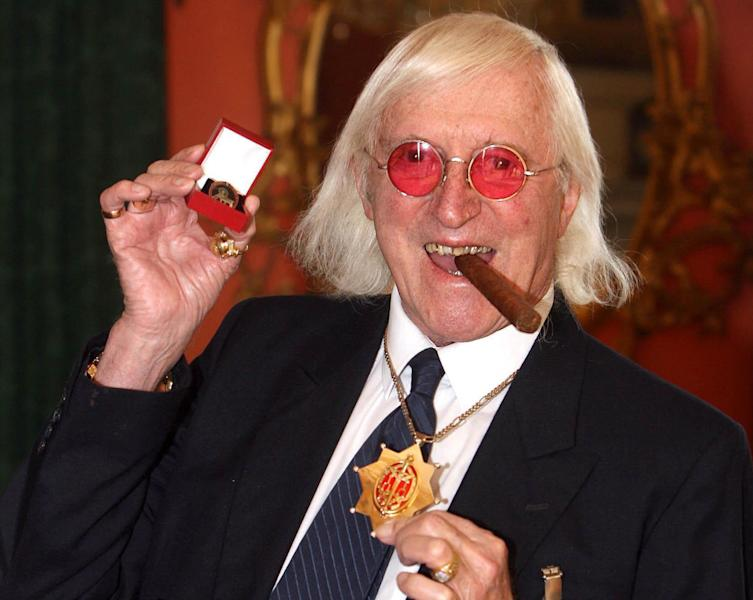 FILE This March 25, 2008 file photo shows Jimmy Savile showing a medal in London. Amid mounting complaints that British authorities for decades failed to properly examine allegations of child abuse, lawmakers called Tuesday Nov. 6, 2012 for a sweeping national inquiry into the issue. Allegations that renowned BBC children's TV host Jimmy Savile abused hundreds of young people have prompted national debate, and led scores of adults to contact authorities about other, unrelated cases of sex offenses in the past. (AP Photo/Lewis Whyld/PA Wire)