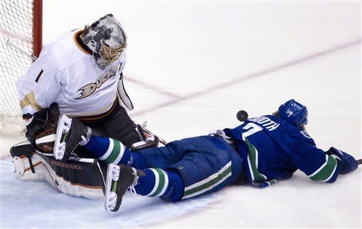 Anaheim Ducks goalie Jonas Hiller (1) looks on as Vancouver Canucks left wing David Booth (7) crashes to the ice after being tripped during first period NHL hockey action at Rogers Arena in Vancouver, British Columbia, Tuesday, April, 3, 2012. (AP Photo/The Canadian Press, Jonathan Hayward)