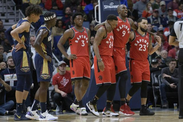Toronto Raptors forward Serge Ibaka (9) leaves the court with the help of guard Fred VanVleet (23) and guard Norman Powell (24) as New Orleans Pelicans guard Jrue Holiday (11) and center Jaxson Hayes (10) watch during the first half of an NBA basketball game in New Orleans, Friday, Nov. 8, 2019. (AP Photo/Matthew Hinton)