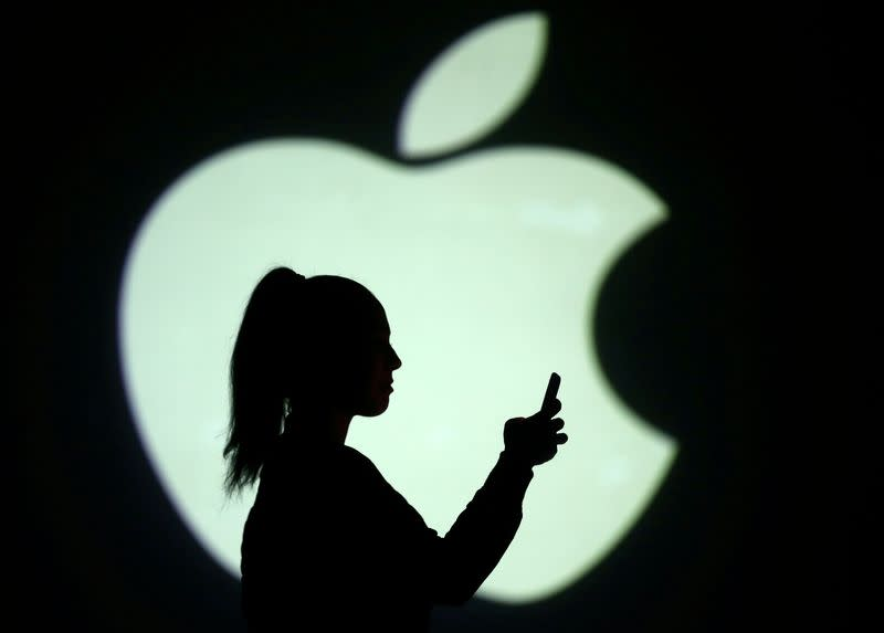 FILE PHOTO: Silhouette of mobile user is seen next to a screen projection of Apple logo in this picture illustration