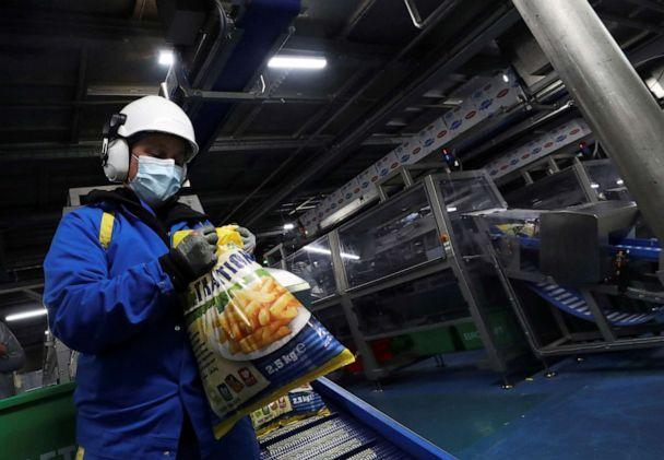 PHOTO: A worker looks at a bag of fresh french fries at Mydibel Group factory, a manufacturer of chilled, frozen and dehydrated potato products, amid the coronavirus pandemic, in Moucron, Belgium, April 29, 2020. (Yves Herman/Reuters)