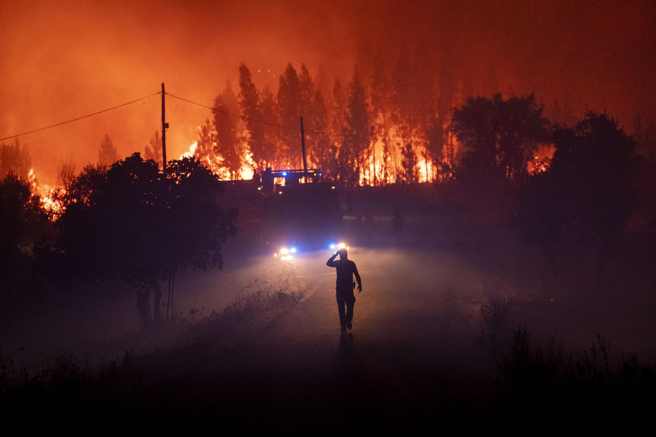 Members of the emergency services try to extinguish a wildfire near Cardigos village, in central Portugal on Sunday, July 21, 2019. About 1,800 firefighters were struggling to contain wildfires in central Portugal that have already injured people, including several firefighters, authorities said Sunday. (AP Photo/Sergio Azenha)