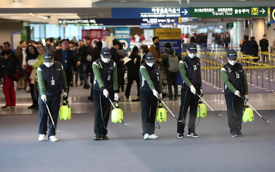 Workers at Incheon International Airport, in South Korea, spray antiseptic solution amid rising concerns over the spread of coronavirus - Suh Myung-geon/Yonhap
