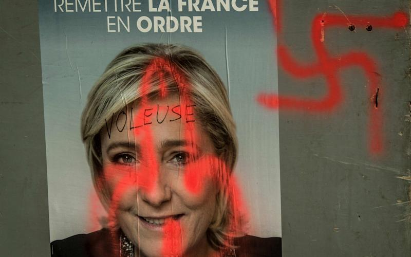 A campaign poster of the far-right Front National candidate Marine Le Pen covered with graffiti, in Caestre, northern France, two days before the first round of the election. - Credit: Philippe Huguen/AFP