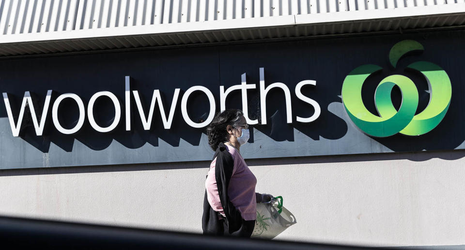 A woman walking past a Woolworths sign wearing a mask.