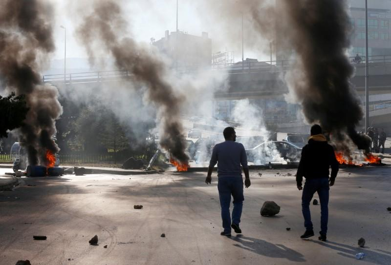 Protestors walk near burning barricades during a protest over economic hardship and lack of new government in Beirut