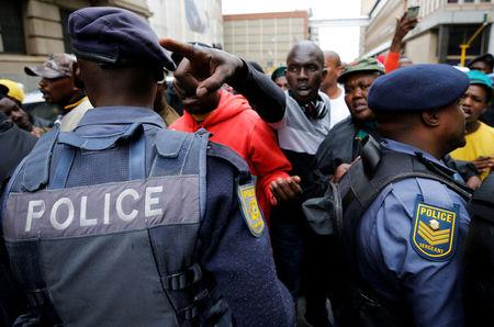 Supporters of the African National Congress (ANC) and South Africa's President Jacob Zuma argue with police in Johannesburg