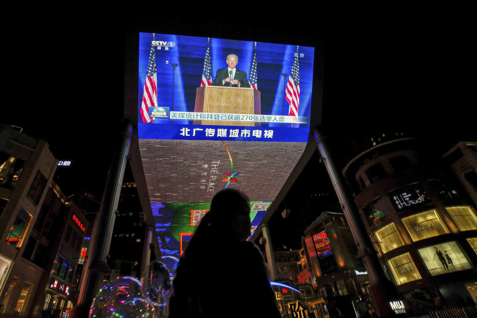 A woman sells balloons near a giant TV screen broadcasting a news of U.S. President-elect Joe Biden delivers his speech, at a shopping mall in Beijing, Sunday, Nov. 8, 2020. World leaders on Sunday cheered Joe Biden's election as U.S. president as a chance to enhance cooperation on climate change, the coronavirus and other problems after four years of President Donald Trump's rejection of international alliances. (AP Photo/Andy Wong)