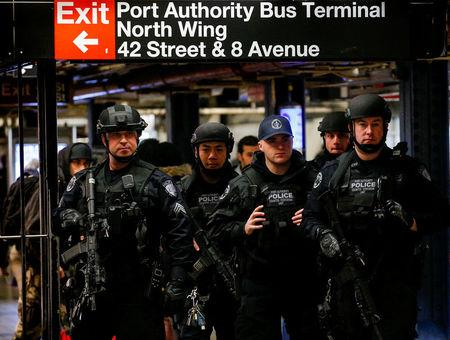 Members of the Port Authority Police Counter Terrorism unit patrol the subway corridor, at the New York Port Authority subway station near the site of an attempted detonation the day before, during the morning rush in New York