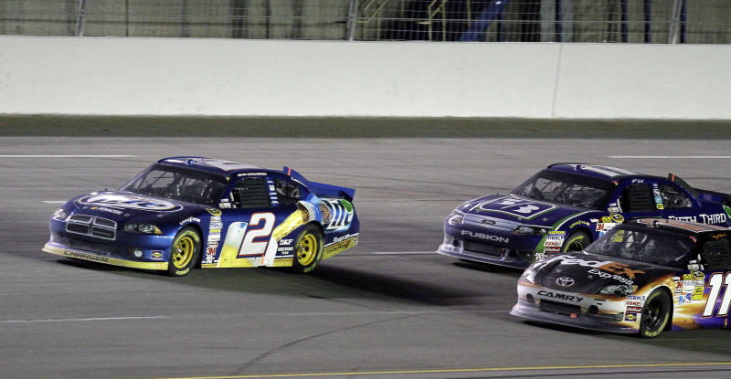 Brad Keselowski (2) takes the lead for good, outrunning Denny Hamlin (11) and and Matt Kenseth on a restart during the NASCAR Sprint Cup series auto race at Kentucky Speedway in Sparta, Ky., Saturday, June 30, 2012. (AP Photo/Garry Jones)