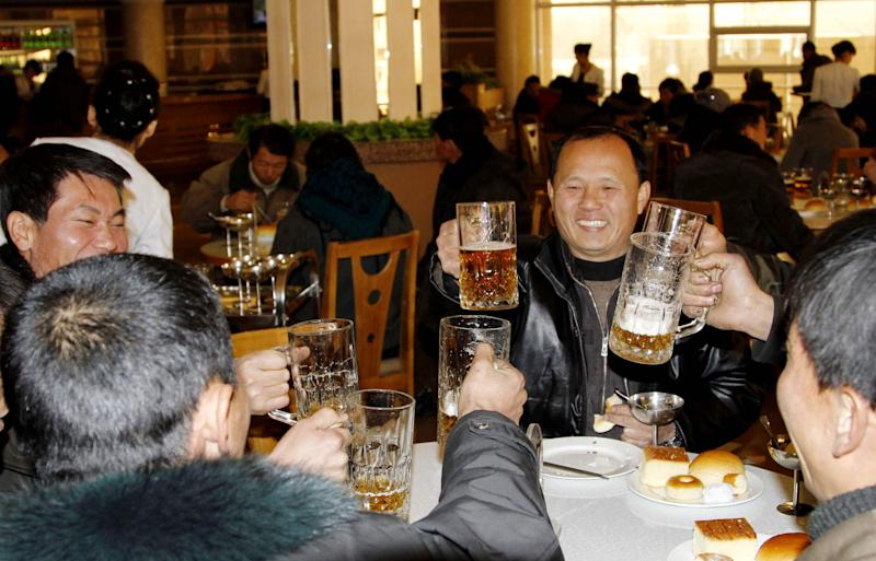 North Koreans toast with beer after hearing the news of a rocket launch at the newly-built Mansukyo Restaurant Wednesday, Dec. 12, 2012 in Pyongyang, North Korea. North Korea appeared to successfully fire a long-range rocket Wednesday, defying international warnings as the regime of Kim Jong Un pushes forward with its quest to develop the technology needed to deliver a nuclear warhead. (AP Photo/Kim Kwang Hyon)
