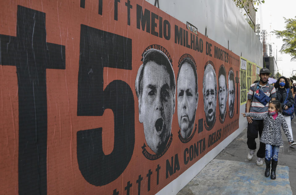 A girl points at a mural featuring the face of Brazilian President Jair Bolsonaro during a protest against his handling of the COVID-19 pandemic along Paulista Avenue, in Sao Paulo, Brazil, Saturday, June 19, 2021. Brazil's COVID-19 death toll is expected to surpass the milestone of 500,000 deaths on Saturday night. (AP Photo/Marcelo Chello)