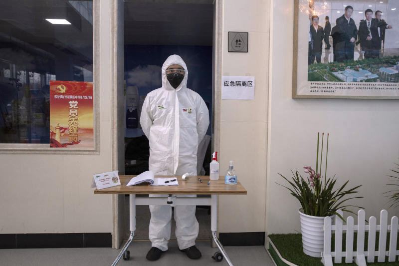 In this Thursday, Feb. 27, 2020, photo,  a worker stands near a picture showing Chinese President Xi Jinping visiting the Mengniu dairy factory in Beijing. Reporters were invited to China Mengniu Dairy Co. Ltd. this week to be shown how companies are reviving after anti-virus measures shut down most of the world's second-biggest economy. (AP Photo/Ng Han Guan)