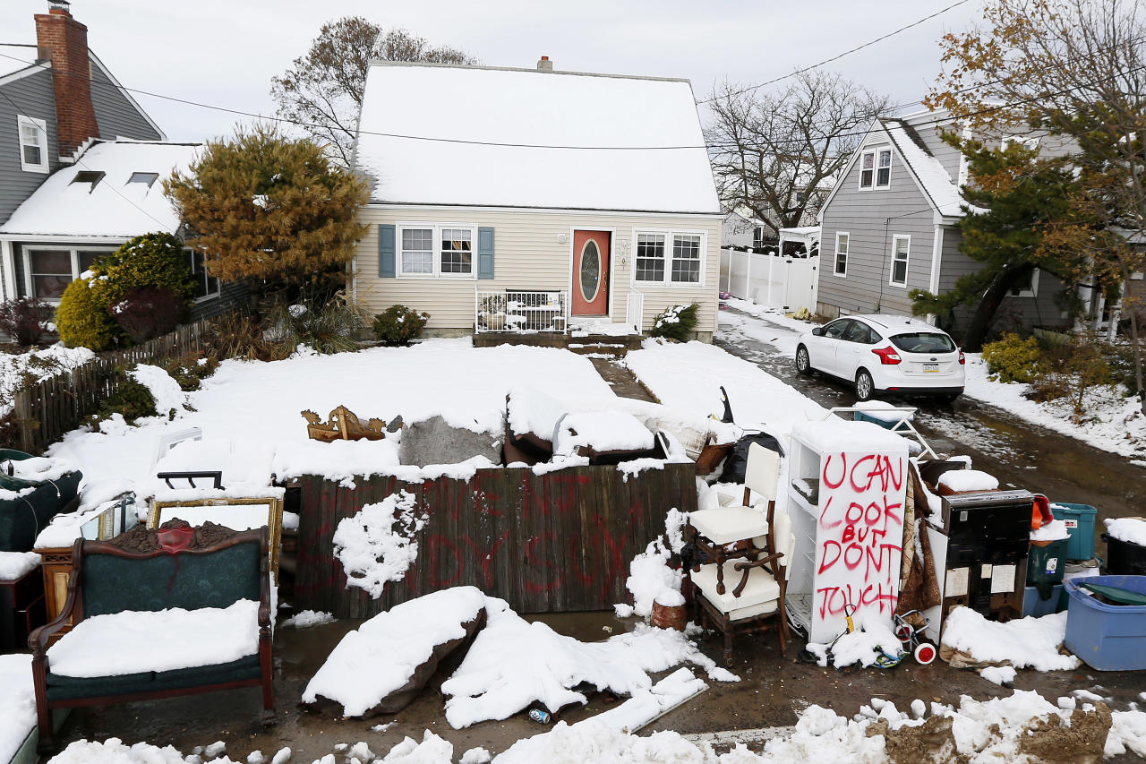 Messages are written on snow covered debris from Superstorm Sandy outside of the Miller residence following a nor'easter storm, Thursday, Nov. 8, 2012, in Point Pleasant, N.J. The New York-New Jersey region woke up to wet snow and more power outages Thursday after the nor'easter pushed back efforts to recover from Superstorm Sandy, that left millions powerless and dozens dead last week. (AP Photo/Julio Cortez)