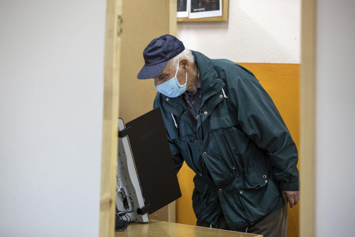 A man casts his ballot in a digital machine during parliamentary elections in the town of during the parliamentary elections in the town of Bankya, Bulgaria, Sunday, April 4, 2021. Bulgarians are heading to the polls on Sunday to cast ballots for a new parliament after months of anti-government protests and amid a surge of coronavirus infections. (AP Photo/Visar Kryeziu)