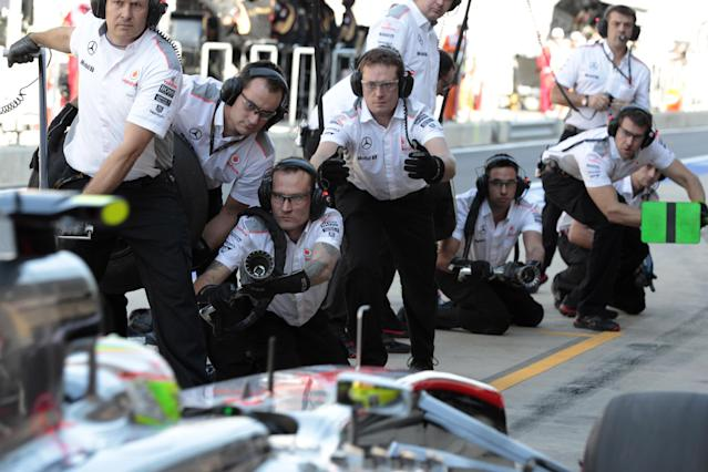 McLaren mechanics wait as driver Sergio Perez of Mexico steers his car into pit lane during the second practice session for the Korean Formula One Grand Prix at the Korean International Circuit in Yeongam, South Korea, Friday, Oct. 4, 2013.(AP Photo/Aaron Favila)