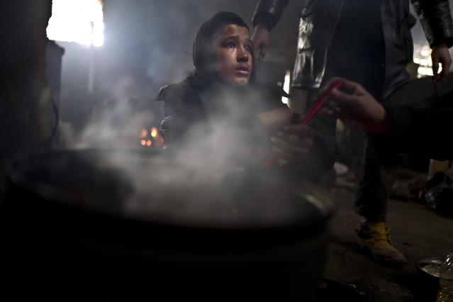 <p>Unaccompanied minor Liaqat, 12, a migrant from Khogyani, Afghanistan, cooks on a fire in an abandoned warehouse where he and other migrants took refuge in Belgrade, Serbia, Feb. 4, 2017. (Photo: Muhammed Muheisen/AP) </p>