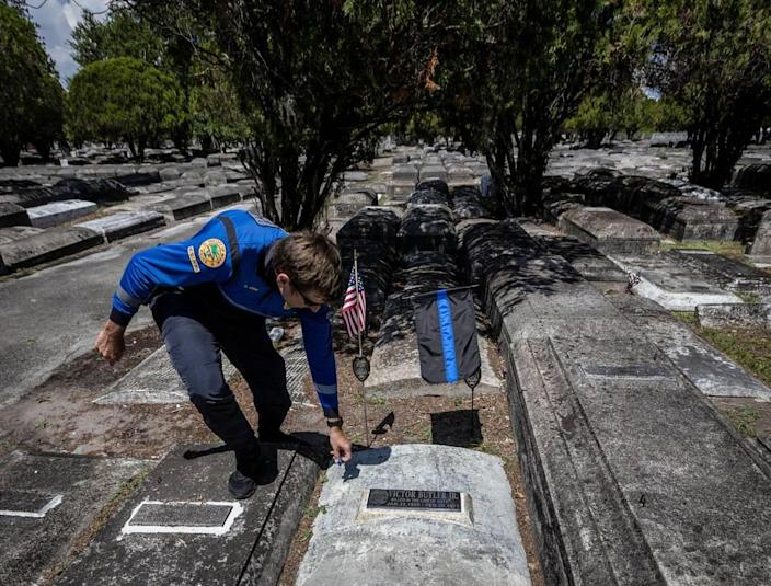 Miami, Florida, May 7 2021 - Commander Dan Kerr pics up debris scattered around the grave of officer Victor Butler who was killed in the line of duty in 1971. Officer Butler's grave is Evergreen Memorial Park in Allapatah.