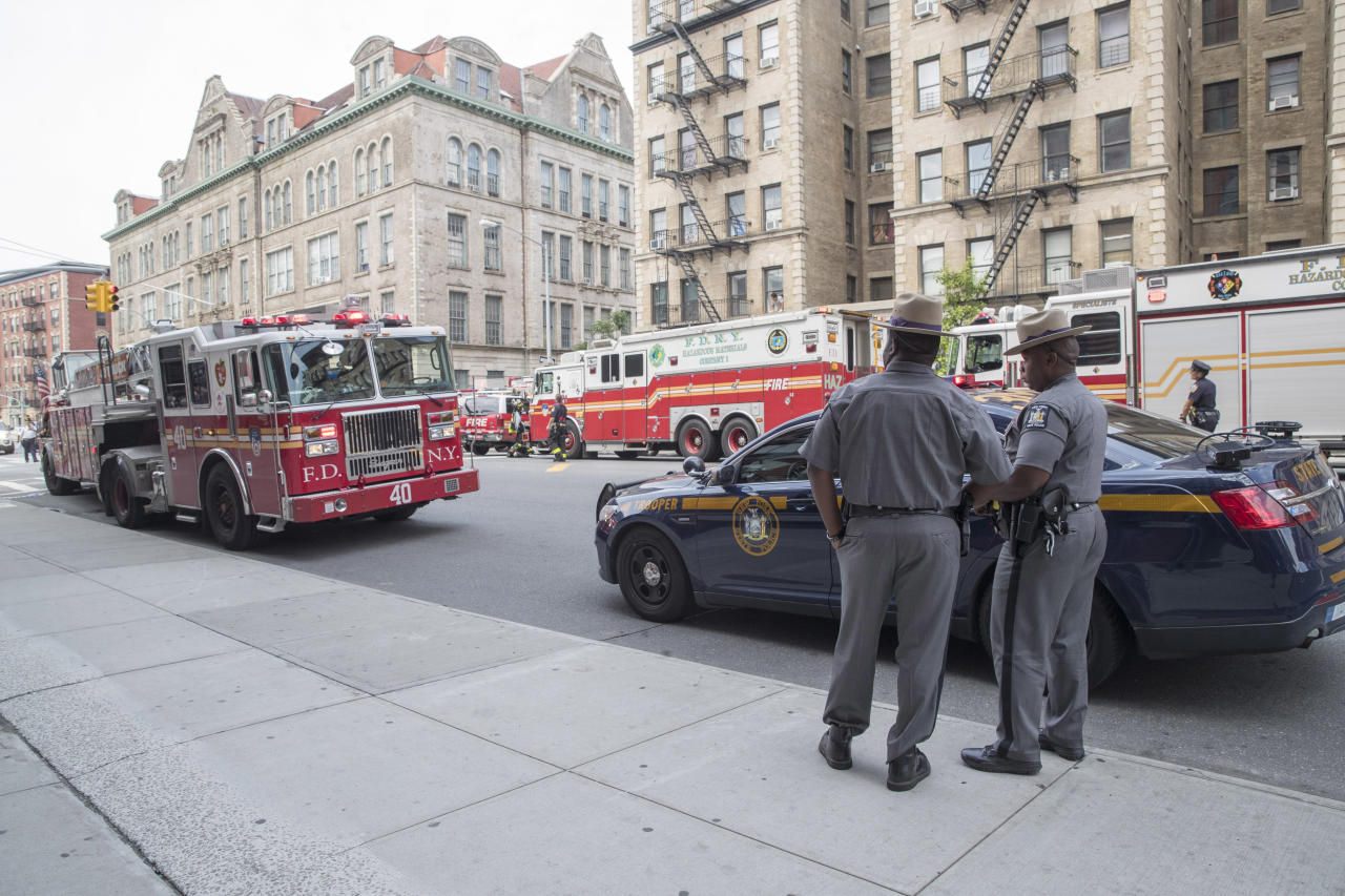 New York State troopers watch as emergency service personnel work at the scene of a subway derailment, Tuesday, June 27, 2017, in the Harlem neighborhood of New York. A subway train derailed near a station in Harlem on Tuesday, frightening passengers and resulting in a power outage as people were evacuated from trains along the subway line. The Fire Department of New York said a handful of people were treated for minor injuries at around 10 a.m. It said there was smoke but no fire. Delays were reported throughout the subway system. (AP Photo/Mary Altaffer)