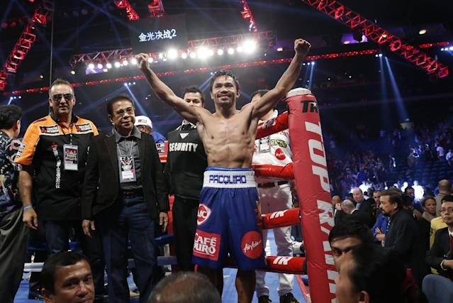 WBO welterweight champion Manny Pacquiao, center, celebrates after defeating WBO junior welterweight champion Chris Algieri of the United States during their welterweight title boxing match at the Venetian Macao in Macau, Sunday, Nov. 23, 2014. Pacquiao got the big knockdowns he desperately craved, battering Algieri around the ring Sunday on his way to a decision win in a lopsided welterweight title fight.(AP Photo/Kin Cheung)