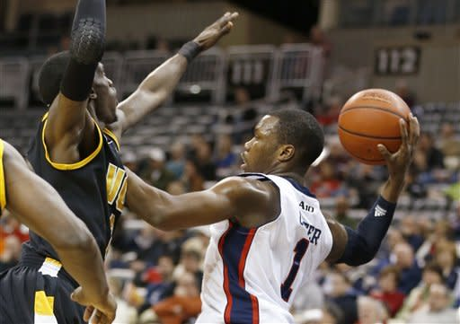 Duquesne's Derrick Colter (1) looks to pass around Virginia Commonwealth's Melvin Johnson in the first half of the NCAA college basketball game on Saturday, Jan. 19, 2013, in Pittsburgh. (AP Photo/Keith Srakocic)