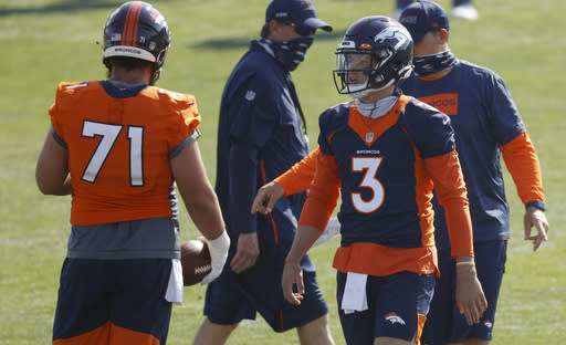 Denver Broncos quarterback Drew Lock, right, confers with guard Austin Schlottmann as they take part in drills at the team's NFL football training camp Friday, Aug. 14, 2020, in Englewood, Colo. (AP Photo/David Zalubowski)