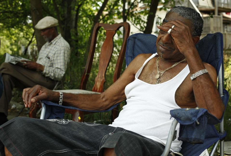 Men who identified themselves as Papa B, left, and Cadillac Bob, find refuge from the heat in a shaded lot between their homes Thursday, July 5, 2012 on Chicago's south side. Chicago hit 103 degrees as oppressive heat slams the middle of the country with record high temperatures that aren't going away after the sun goes down. (AP Photo/Sitthixay Ditthavong)